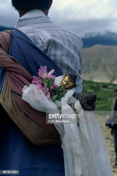 Nepal Mustang Buddha figure wrapped in ceremonial scarves being carried through the summer fields during Lok Khor festival to bring good harvests and...