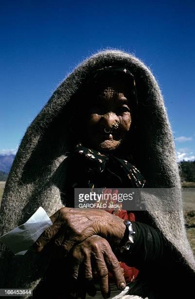 Nepal Népal mars 1970 Portrait d'une vieille femme recouverte d'une couverture en pashmini sur sa tête anneaux et bijoux à son nez et bracelet en...
