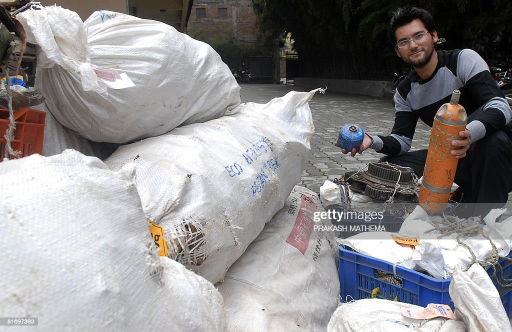 Nepal-environment-Everest-mountaineering-waste,INTERVIEW by Sam Taylor Nepalese mountaineer Dawa Steven Sherpa poses with garbage he has collected from expeditions to the Everest region in Kathmandu on June 24, 2008. The young mountaineer from Nepal has claimed a major breakthrough in his bid to promote eco-friendly climbing on Mount Everest, with his team reaching extraordinary heights of cleanliness. Expedition leader Dawa Steven Sherpa has made it his mission to clean up the world's highest peak, and at the same revolutionise big mountain climbing by giving out some badly needed toilet training. AFP PHOTO/Prakash MATHEMA