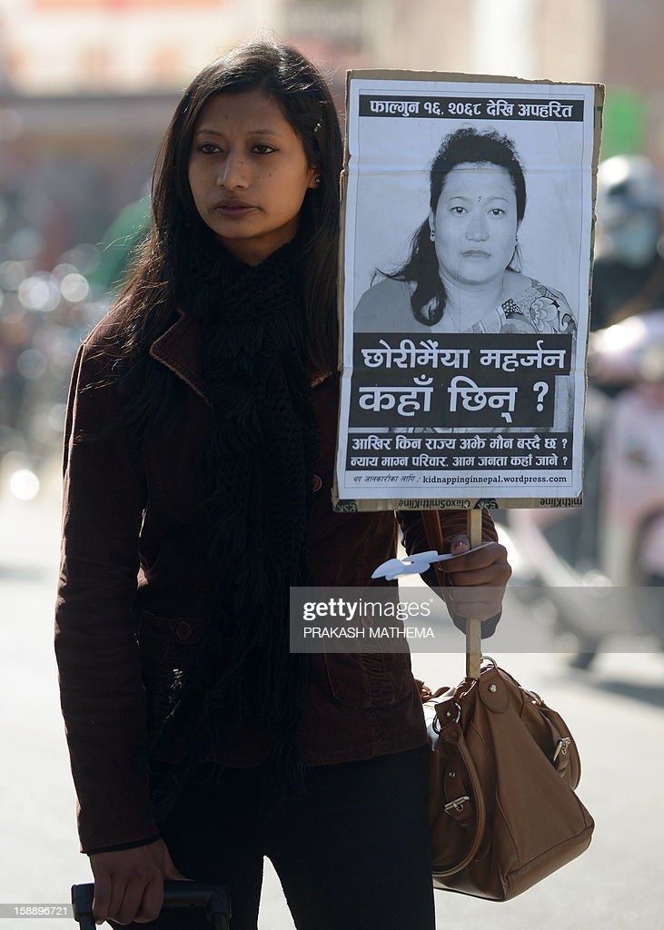 A Nepalese activist holds a placard as she stands near the Prime Minister's residence in Kathmandu on January 3, 2013, during a protest demanding justice in rising cases of violence against women. Hundreds of Nepalese campaigners have protested over the alleged rape and robbery of a maid by government officials, echoing widespread anger in neighbouring India over violence against women. AFP PHOTO/Prakash MATHEMA