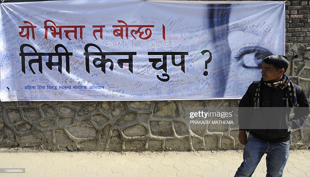 A Nepalese activist looks at a banner as he stands near the Prime Minister's residence in Kathmandu on January 3, 2013, during a protest demanding justice in rising cases of violence against women. Hundreds of Nepalese campaigners have protested over the alleged rape and robbery of a maid by government officials, echoing widespread anger in neighbouring India over violence against women. AFP PHOTO/Prakash MATHEMA