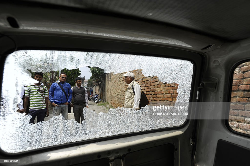 Nepalese activists are pictured through the broken window of a government van during a demonstration against the Constitutional Council's appointment of Lokman Singh Karki as Commission for the Investigation of Abuse of Authority chief, in Kathmandu on May 8, 2013. Dozens of rights activists and student organisations have been protesting since the start of the week over the decision to appoint Lokman Singh Karki to run the Commission for the Investigation of Abuse of Authority. AFP PHOTO/ Prakash MATHEMA