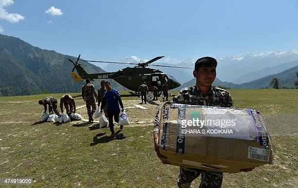 A Nepalese Army soldier carries relief food parcels from an Nepal Army military transport helicopter to an army camp in the village of Rasuwa on May...