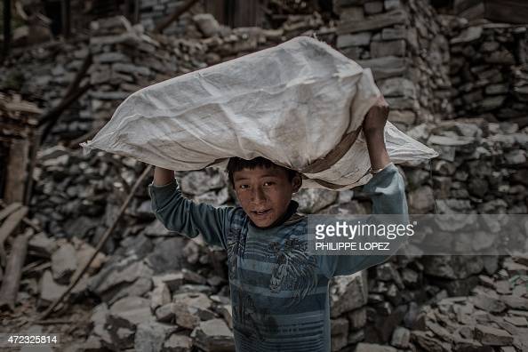 A Nepalese arthquake survivor carries relief supplies delivered by a World Food Programme helicopter in the remote Kerauja village in Gorkha district...