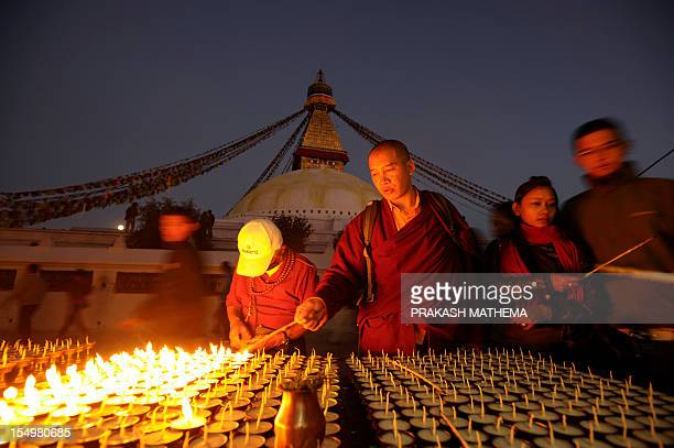 A Nepalese Buddhist monk lights a candle at the Boudhanath Stupa during a full moon festival in Kathmandu on October 29 2012 The Boudhanath Stupa...