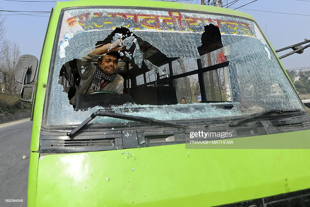 A Nepalese bus driver clears the broken glass of his winshield after his bus was vandalised during a strike in Kathmandu on March 7, 2013. The nationwide strike was organised by an alliance of leftist parties and crippled daily life across the country for the second day in a row. AFP PHOTO/ Prakash MATHEMA