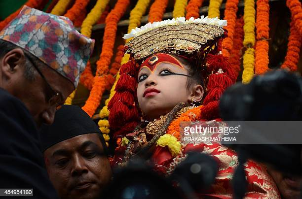 A Nepalese child revered as a living goddess or Kumari is carried during a procession on the main day of the Indra Jatra festival at Basantapur...