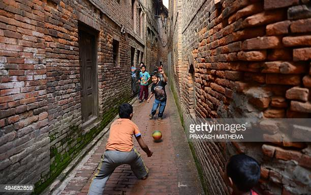 Nepalese children play football in a passageway near the Durbar Square in Bhaktapur some 12 kilometers southeast of Kathmandu on May 30 2014 Over 80...