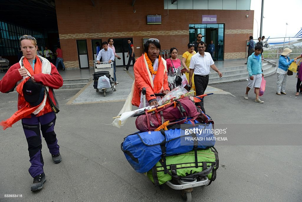 Nepalese climber Phurba Tenjing Sherpa(C) arrives at an airport in Kathmandu on May 24, 2016, after he successfully summitted Mount Everest for the tenth time. Rescuers searching for two Indian climbers missing on Mount Everest said that there was little hope of finding the pair alive after losing contact with them over the weekend. The two men -- identified by the Indian embassy as Paresh Nath and Goutam Ghosh -- were near the summit of the 8,848-metre (29,029-foot) mountain on May 21, when they lost contact with the rest of their team. MATHEMA