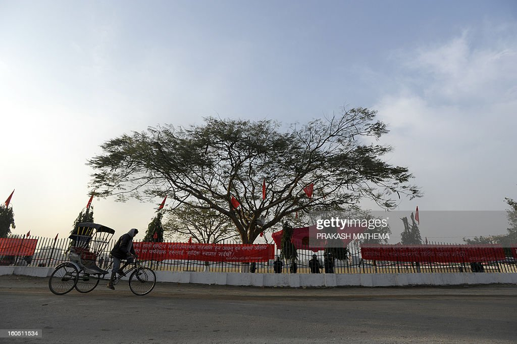 A Nepalese cycle rickshaw driver pedals past the venue of the Unified Communist Party of Nepal (Maoist) general convention at Hetauda, some 100 kms south of Kathmandu on Febuary 2, 2013. Thousands of Nepal's former rebel Maoists are due to gather Saturday for their biggest show of strength since taking up arms in a 10-year insurgency and toppling the world's last Hindu monarchy. AFP PHOTO/Prakash MATHEMA