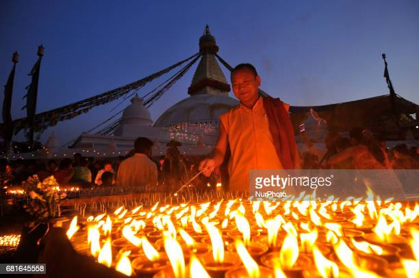 Nepalese devotee offering butter lamps at the premises of Boudhanath Stupa during celebration the 2561 Buddha Purnima festival Birth Anniversary of...