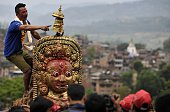 A Nepalese devotee shouts to Hindu and Buddhist residents as they pull a chariot during the Rato Machindranath Chariot Festival at Bungamati in...