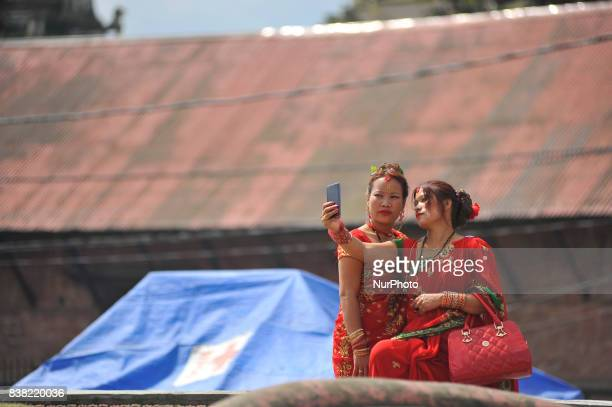 Nepalese devotee taking selfie from mobile after offering ritual prayer during Teej festival celebrations at Pashupatinath Temple Kathmandu Nepal on...
