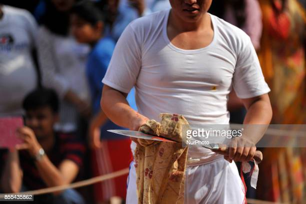 A Nepalese devotees cleans KHUKURI as after slaughter a goat on the occasion of Navami ninth day of Dashain Festival at Basantapur Durbar Square...