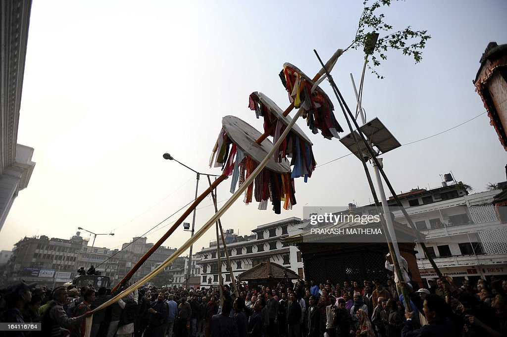 Nepalese devotees erect a ceremonial bamboo pole know as a 'Chir', fringed with strips of cloth and representing good luck charms, on the first day of Holi, the festival of colours at Basantapur Durbar Square in Kathmandu on March 20, 2013. The Holi festival is celebrated all over the country to mark the victory of God Rama over Rawan, the King of Evil and symbolises the arrival of the spring season. The final day of Holi festival falls on March 26, 2013. AFP PHOTO/Prakash MATHEMA