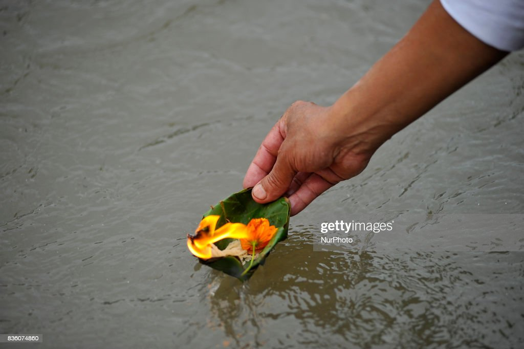 Nepalese Devotees offering religious puja along with butter lamps after Holy Bath on the banks of the Bagmati River during the celebration of Kuse Aunsi or Father's Day at Gokarna Temple in Kathmandu, Nepal on Monday, August 21, 2017. On the day of the new moon, families also pay their respects to their deceased fathers.