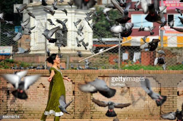Nepalese devotees plays with peigons after offering ritual prayer during Teej festival celebrations at Pashupatinath Temple Kathmandu Nepal on...
