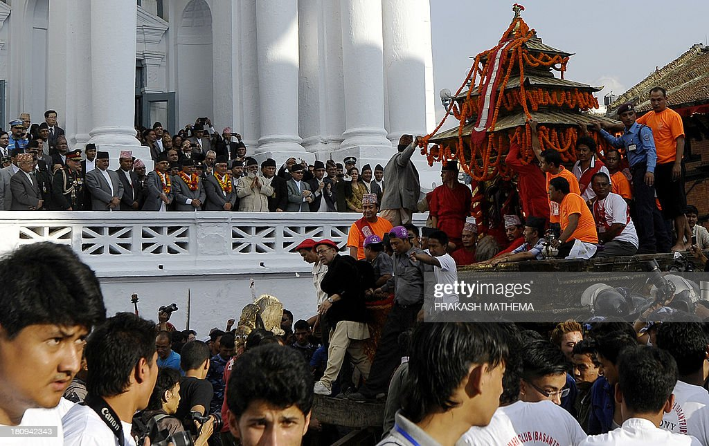 Nepalese devotees pull the chariot carrying Kumari, the prepubescent girl revered in Nepal as a living goddess, as dignitaries watch on the main day of the Indra Jatra festival at Basantapur Durbar Square in Kathmandu on September 18, 2013. Nepal's week-long festival celebrates 'Indra', the king of gods and the god of rains. Every September, the living goddess is carried in a palanquin in a religious procession through parts of the Nepalese Capital. AFP PHOTO/ Prakash MATHEMA