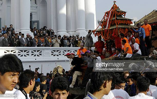 Nepalese devotees pull the chariot carrying Kumari the prepubescent girl revered in Nepal as a living goddess as dignitaries watch on the main day of...