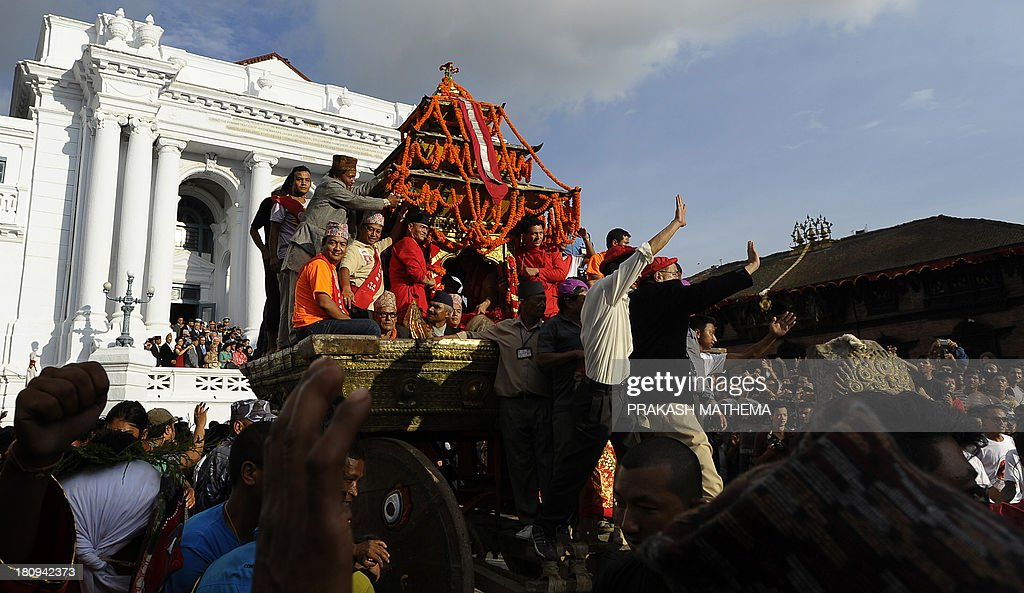 Nepalese devotees pull the chariot carrying Kumari, the prepubescent girl revered in Nepal as a living goddess, on the main day of the Indra Jatra festival at Basantapur Durbar Square in Kathmandu on September 18, 2013. Nepal's week-long festival celebrates 'Indra', the king of gods and the god of rains. Every September, the living goddess is carried in a palanquin in a religious procession through parts of the Nepalese Capital. AFP PHOTO/ Prakash MATHEMA