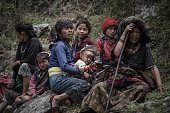 Nepalese earthquake survivors look on as relief supplies are delivered by a World Food Programme helicopter in the remote Kerauja village in Gorkha...