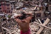 Nepalese earthquake victims looks on among debris of collapsed buildings on April 29 2015 in Bhaktapur Nepal A major 78 earthquake hit Kathmandu...