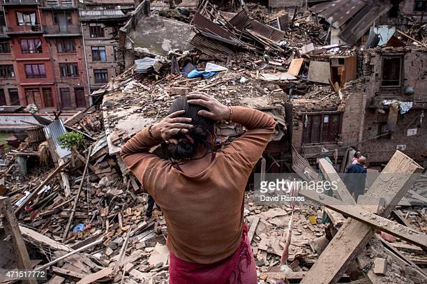 Nepalese earthquake victims looks on among debris of collapsed buildings on April 29 2015 in Bhaktapur Nepal A major 78 earthquake hit Kathmandu...