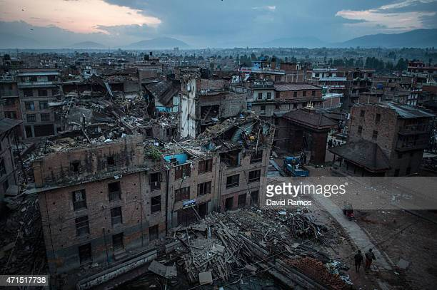 Nepalese earthquake victims walk among debris of collapsed buildings on April 29 2015 in Bhaktapur Nepal A major 78 earthquake hit Kathmandu midday...