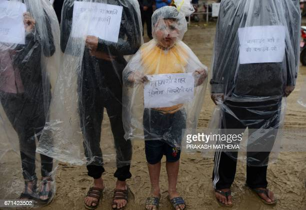 TOPSHOT Nepalese environmental activists take part in a protest to mark Earth Day by covering themselves in plastic sheets to protest against air...