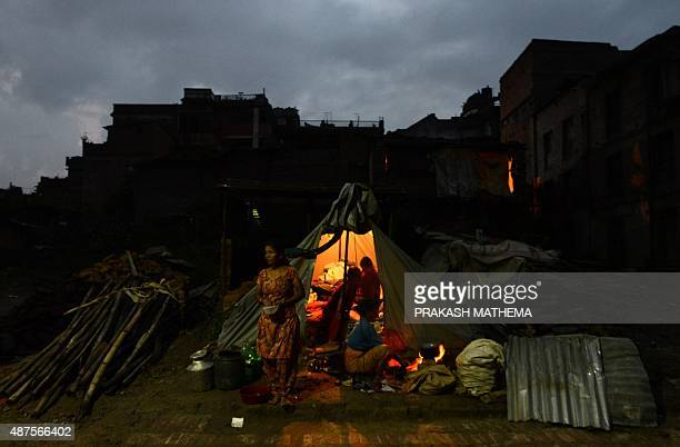 A Nepalese family prepares food next to their tent near earthquakedamaged houses in Bhaktapur on the outskirts of Kathmandu on September 10 2015 Twin...