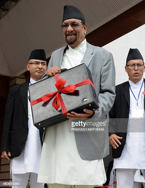 Nepalese Finance Minister Ram Sharan Mahat carries a briefcase with the new government's budget for fiscal year 2015/2016 in Kathmandu on July 14...