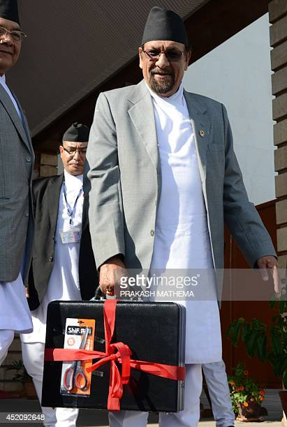Nepalese Finance Minister Ram Sharan Mahat poses with the briefcase containing the new government's budget for the fiscal year 2014/2015 in Kathmandu...