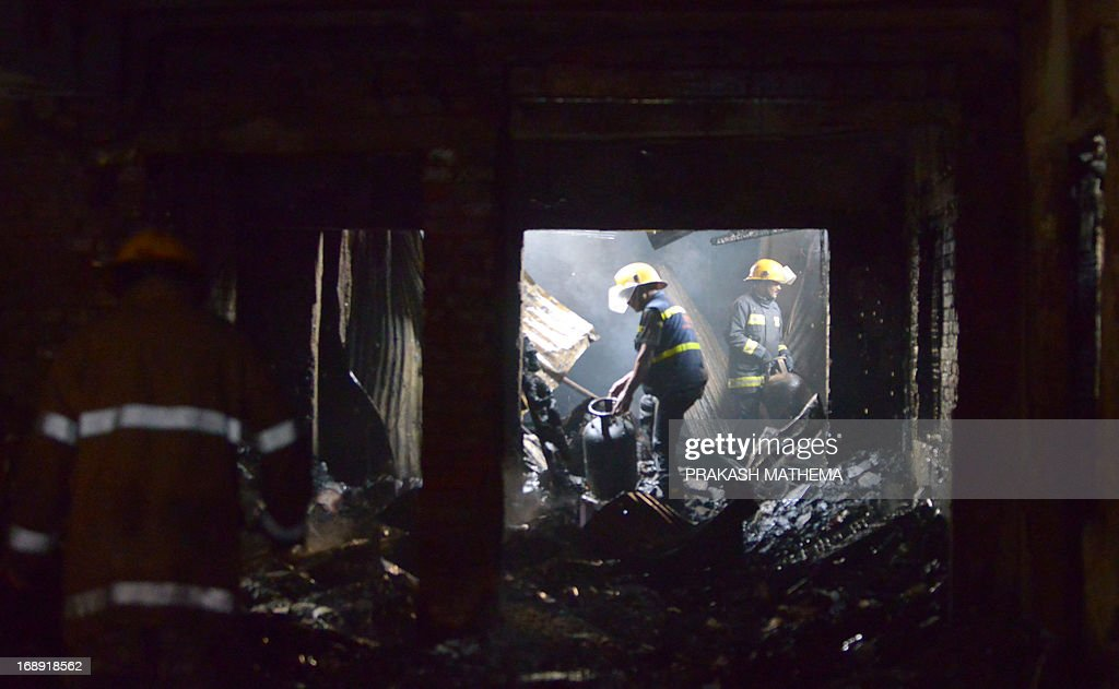 Nepalese firefighters clear debris after a fire at 'Pilgrims Book House' in Kathmandu on May 17, 2013. A massive fire broke out in the tourist hub of Thamel in the Nepalese capital with the bookshop, adjoining jewellery and curio shops completely destroyed. AFP PHOTO/Prakash MATHEMA