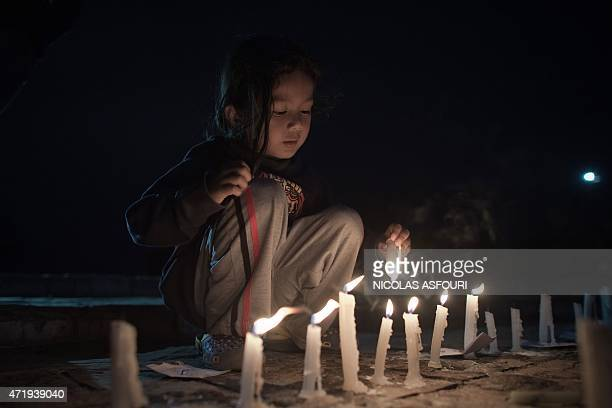 A Nepalese girl lights candles during a candle light vigil in Kathmandu on May 2 a week after the 78 magnitude earthquake struck the Himalayan nation...