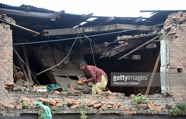 A Nepalese girl takes out belongings from her damaged house in Bhaktapur on the outskirts of Kathmandu on April 26 2015 International aid groups and...