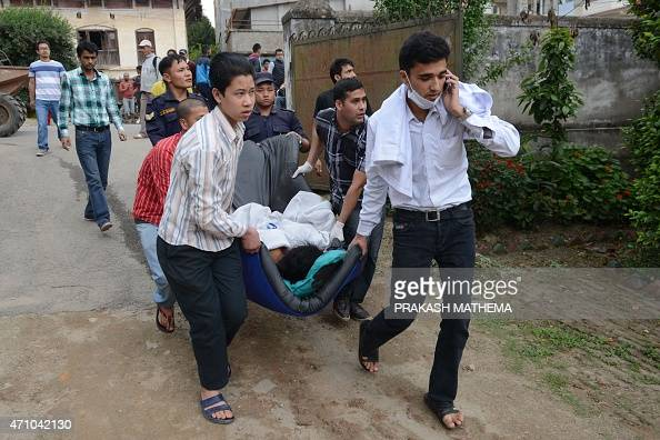Nepalese health workers carry injured people into an open area following an 79 earthquake at Lalitpur on the outskirts of Kathmandu on April 25 2015...
