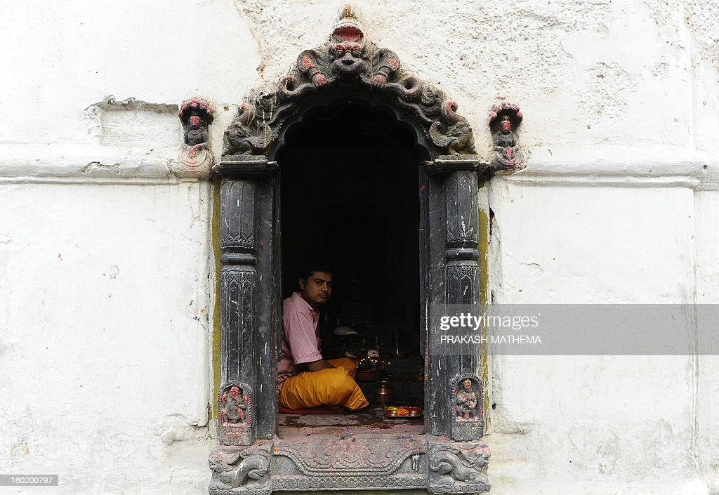 A Nepalese Hindu Brahmin priest looks out from a window during the Rishi Panchami festival in Kathmandu on September 10, 2013.Rishi Panchami marks the end of the three-day long Teej festival, in which married women fast and pray for the good health of their husbands to Shiva, the Hindu god of destruction, while unmarried women wish for handsome husbands and happy conjugal lives. AFP PHOTO/Prakash MATHEMA