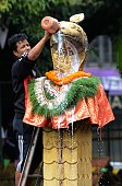 A Nepalese Hindu devotee pours an offering of milk over a statue of the snake god known as 'Nag' at Nagpokhari in Kathmandu on August 19 2014 The...