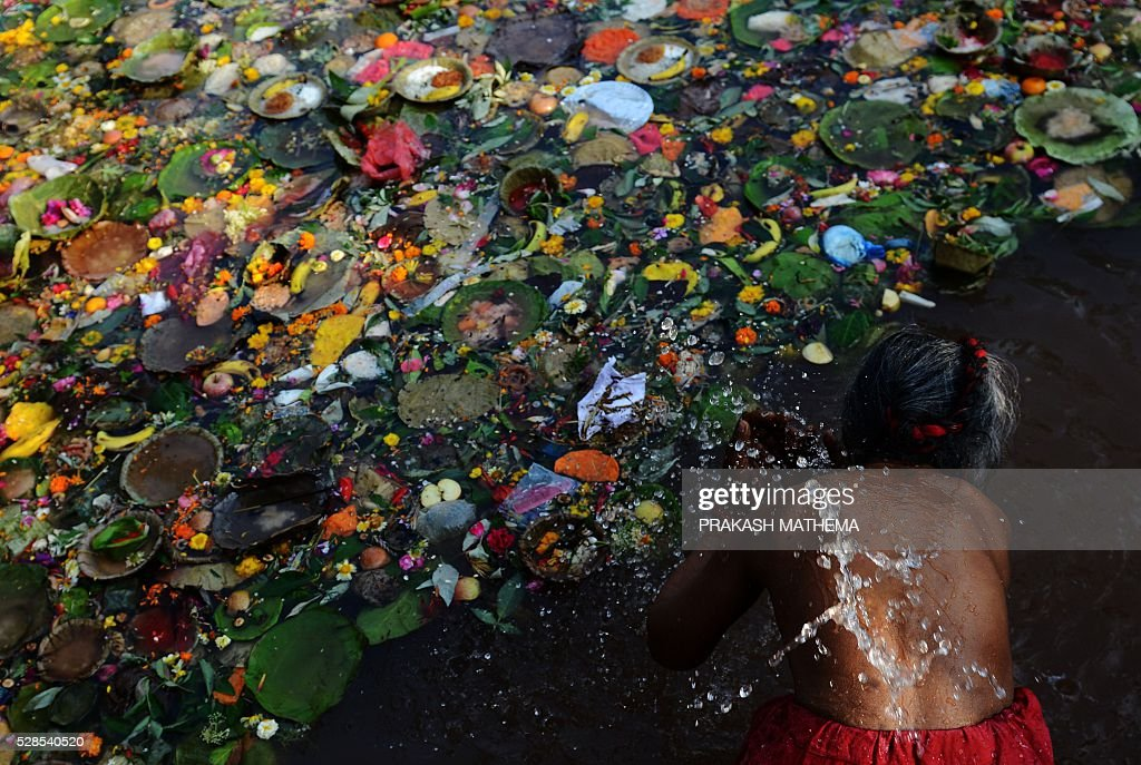 A Nepalese Hindu devotee takes a holy bath as they mark the Mother's Day Festival at Matathirtha on the outskirts of Kathmandu on May 6, 2016. Nepalese Hindu devotees come from across the country to bathe, offer prayers and leave offerings at the Matathirtha Temple during the event, which honours mothers who have passed away. / AFP / PRAKASH