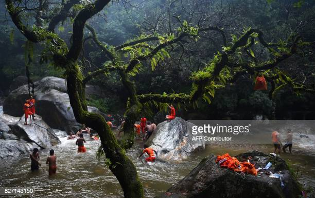 TOPSHOT Nepalese Hindu devotees bath and collect water in the Bagmati river on their way to the Pashupatinath temple to offer prayers to Lord Shiva...
