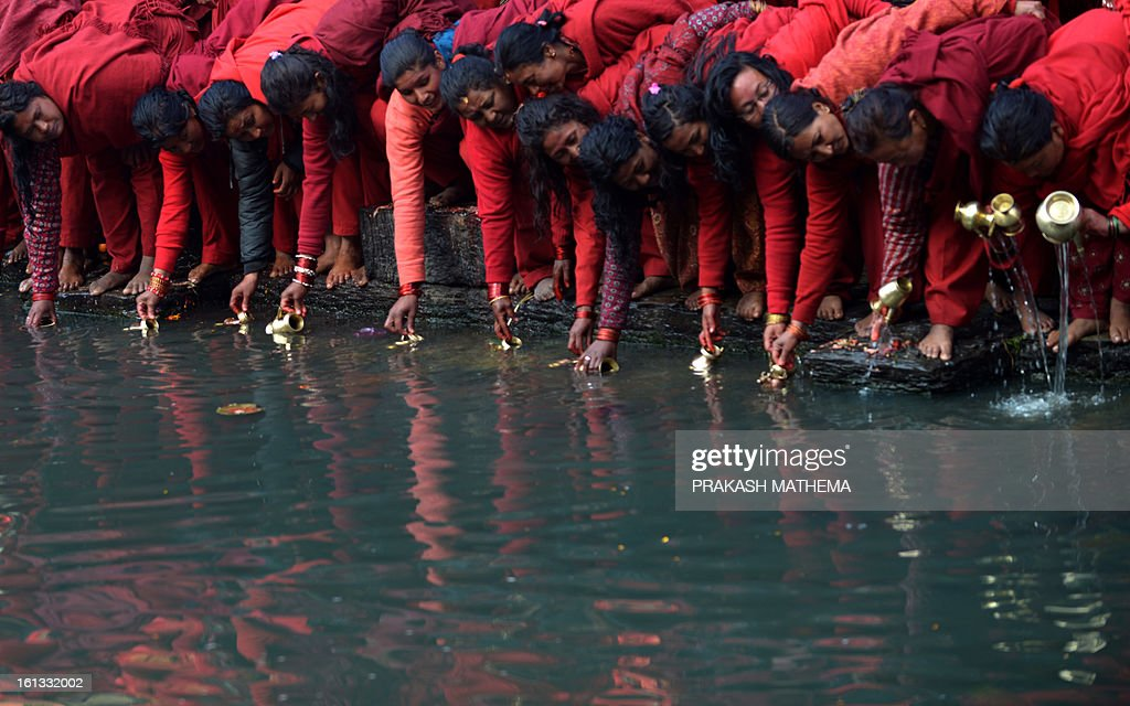 Nepalese Hindu devotees fill water pots from the holy Bagmati River at the Pashupatinath Temple during the month-long Swasthani festival in Kathmandu on February 10, 2013. Scores of married and unmarried women in the Himalayan nation are marking the month-long fast in the hope of a prosperous life and conjugal happiness. AFP PHOTO/Prakash MATHEMA
