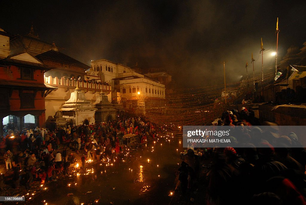 Nepalese Hindu devotees gather to observe the Balachaturdashi festival at the Pashupatinath temple in Kathmandu on December 12, 2012. Devotees sow seven kinds of seeds paddy, barley, sesame, wheat, gram, maize, and finger millet around temple premises in the name of their departed family members during the year in observance of the festival. AFP PHOTO/ Prakash MATHEMA