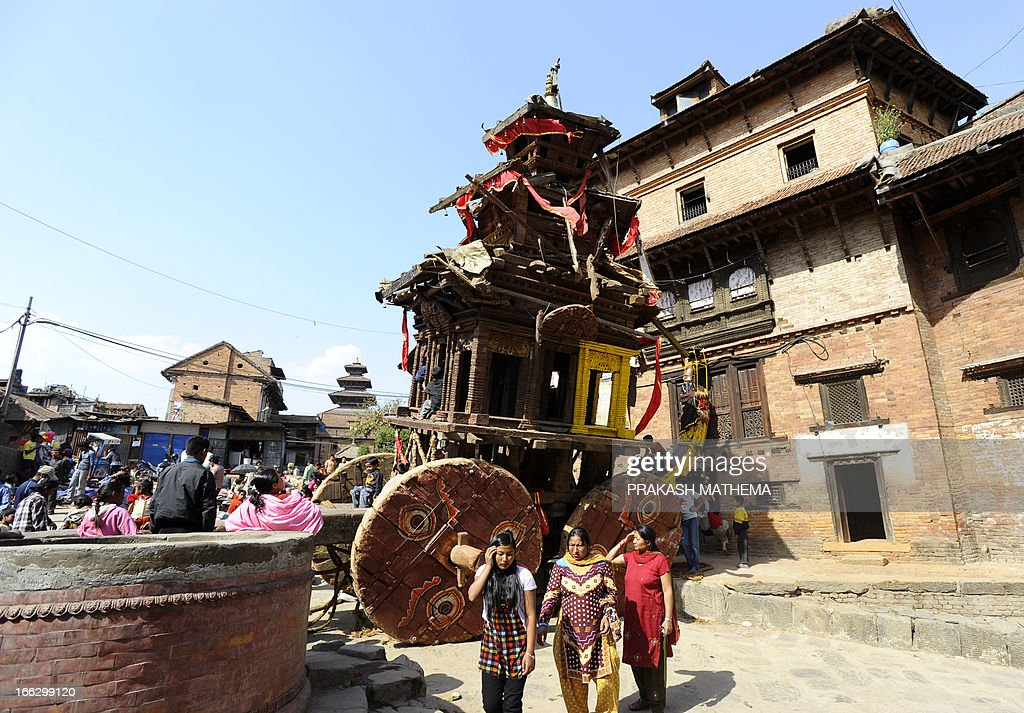 Nepalese Hindu devotees look on near a wooden chariot during a second day of Bisket Jatra, a festival in Bhaktapur, some 12 kms east of Kathmandu on April 11, 2013. Two people died in Nepal after being crushed under the wheels of a 10-metre-high (35-foot) wooden chariot being used during a new year festival that descended into chaos, police said. AFP PHOTO/ Prakash MATHEMA