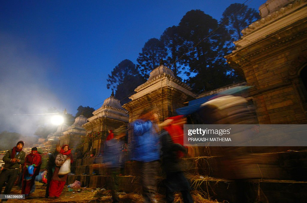 Nepalese Hindu devotees plant seeds during the Balachaturdashi festival at the Pashupatinath temple in Kathmandu on December 12, 2012. Devotees sow seven kinds of seeds paddy, barley, sesame, wheat, gram, maize, and finger millet around temple premises in the name of their departed family members during the year in observance of the festival. AFP PHOTO/ Prakash MATHEMA