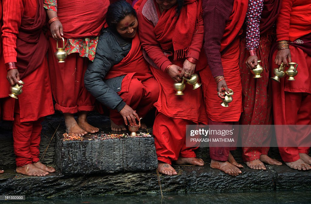 Nepalese Hindu devotees prepare to fill water pots from the holy Bagmati River at the Pashupatinath Temple during the month-long Swasthani festival in Kathmandu on February 10, 2013. Scores of married and unmarried women in the Himalayan nation are marking the month-long fast in the hope of a prosperous life and conjugal happiness. AFP PHOTO/Prakash MATHEMA