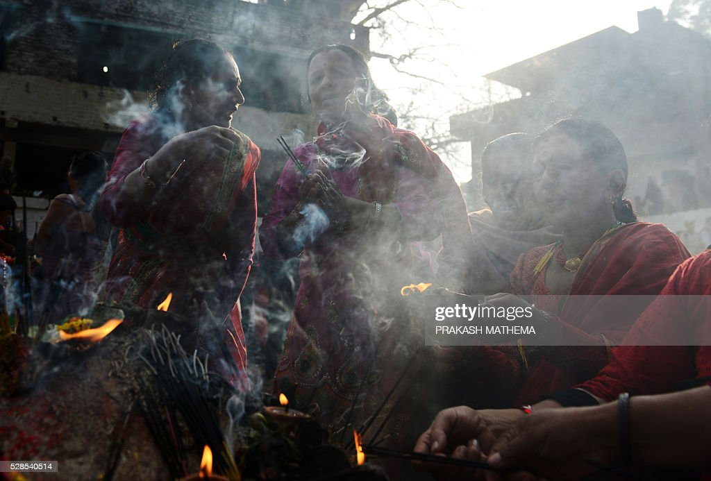 Nepalese Hindu devotees take a holy bath as they mark the Mother's Day Festival at Matathirtha on the outskirts of Kathmandu on May 6, 2016. Nepalese Hindu devotees come from across the country to bathe, offer prayers and leave offerings at the Matathirtha Temple during the event, which honours mothers who have passed away. / AFP / PRAKASH