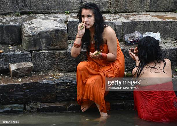 A Nepalese Hindu girl brushes her teeth before taking a ritual bath in the Bagmati river during the Rishi Panchami festival in Kathmandu on September...