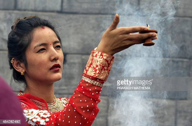 A Nepalese Hindu woman dressed in red pays homage to Shiva the Hindu god of destruction as she celebrates the Teej festival at the Pashupatinath...