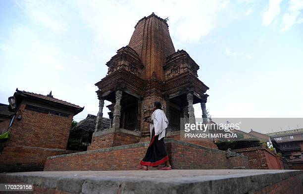 A Nepalese Hindu woman leaves a temple in Bhaktapur Durbar Square area in Bhaktapur some 12 kilometres southeast of Kathmandu on June 11 2013...