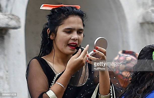 A Nepalese Hindu women does her make up after performing ritual bath in the Bagmati River during the Rishi Panchami festival in Kathmandu Nepal...